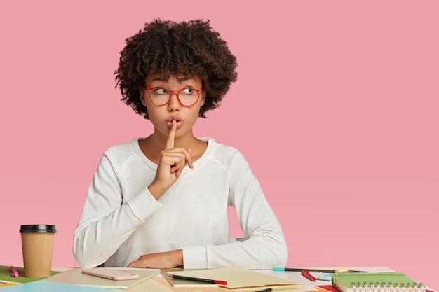 La foto dell'architetto femminile segreto dalla pelle scura fa il gesto del silenzio, indossa occhiali trasparenti Foto Gratuite
