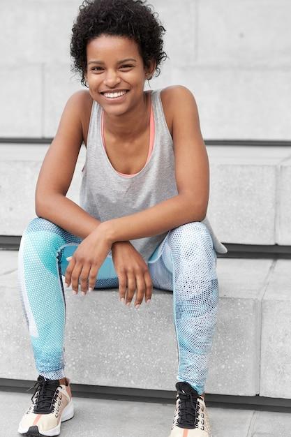Foto di una donna nera sicura di sé in abiti sportivi, ha un'espressione felice e rilassata, sorride ampiamente, è felice di vincere le competizioni sportive, si siede sulle scale, pronta a raggiungere nuovi obiettivi. etnia, sport Foto Gratuite