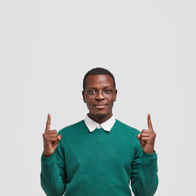 Photo of serious dark skinned man with confident facial expression, indicates with both index fingers upside, wears spectacles and green jumper Free Photo