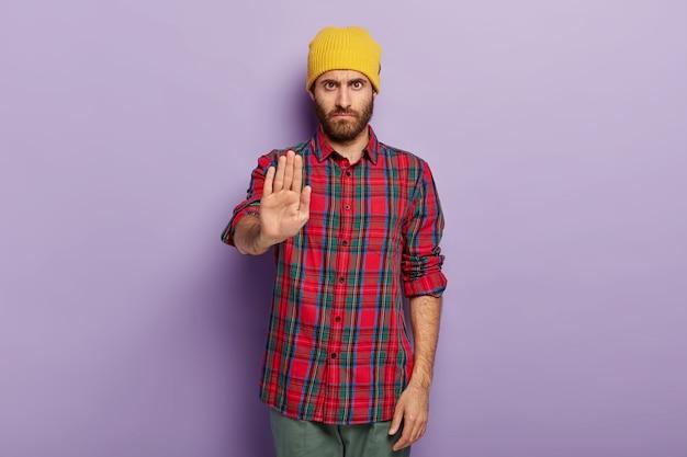 La foto dell'uomo serio con la barba lunga severa mostra il gesto di arresto, vestito con abiti alla moda, rifiuta qualcosa, chiede di non compiere azioni proibite Foto Gratuite