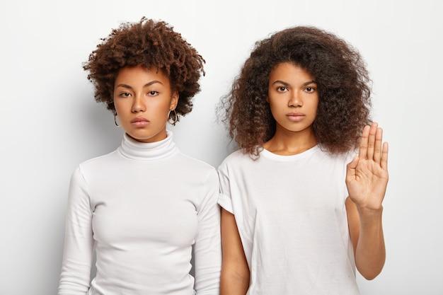 La foto di due donne afro gravi ha i capelli ricci e folti, una femmina fa il gesto di arresto Foto Gratuite