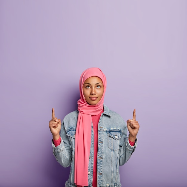 Photo of serious young muslim woman points upwards with both fore fingers, wears pink scarf, wears pink and denim jacket, isolated over purple wall. people, advertisement and promotion. Free Photo