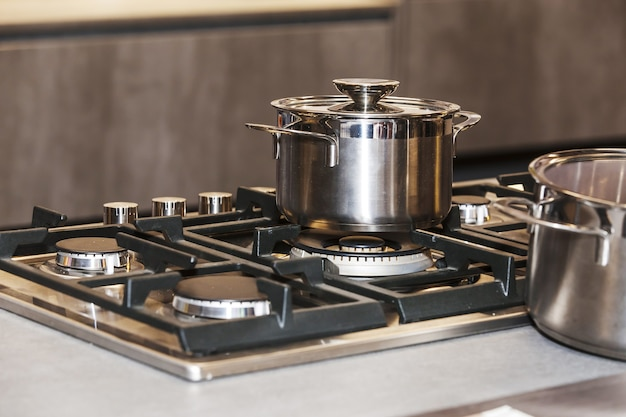 Photo of shiny metal pan on a gas stove, shallow dof focus on pan Premium Photo