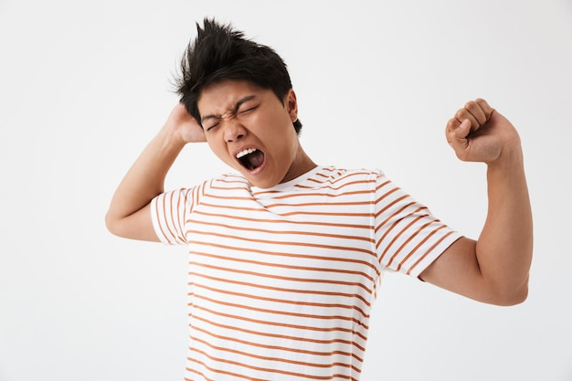 Photo of sleepy asian man with brown hair in casual t-shirt yawning after sleepless night or overwork, isolated Premium Photo