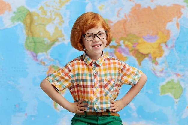 Foto di ragazzo sorridente con i capelli rossi, con gli occhiali, tenendo le mani sulla vita, avendo gioia stando in piedi contro la mappa Foto Gratuite
