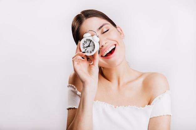 Foto di bruna sorridente senza trucco in posa con l'orologio sul muro bianco. Foto Gratuite