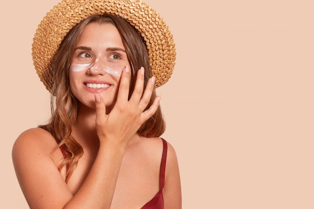 Photo of smiling woman with long hair, has happy facial expression, applaying sunscreen, wearing straw hat, wanting to tan, isolated on beige wall. summertime, vacation, sunscreen concept. Premium Photo