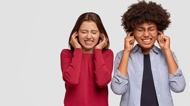 Foto di ragazze stressanti stringono i denti, tappano le orecchie, ignorano il suono sgradevole, stanno in piedi da vicino, vestite con abiti casual, isolate su un muro bianco con spazio libero per la tua pubblicità o promozione Foto Gratuite