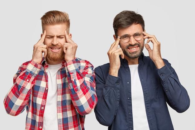La foto di due uomini stressanti ha mal di testa, tiene gli anteriori sulle tempie, ha un'espressione del viso contrariata Foto Gratuite