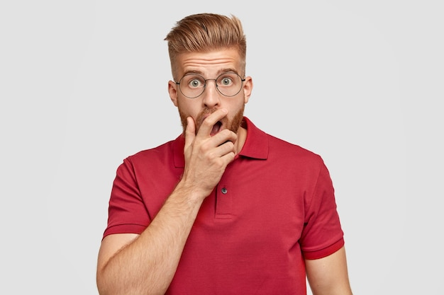 Photo of stupefied ginger hipster covers mouth with hand, afraids of something Free Photo