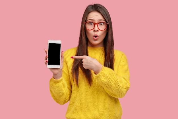 La foto della donna attraente sorpresa indica lo schermo vuoto vuoto del gadget moderno, mantiene la mascella aperta, indossa abiti gialli Foto Gratuite
