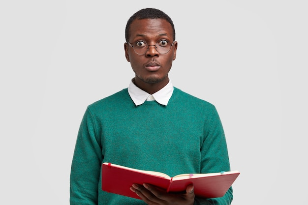 Photo of surprised black male teacher looks directly at camera, wears spectacles, carries notepad with notes, conducts lecture Free Photo