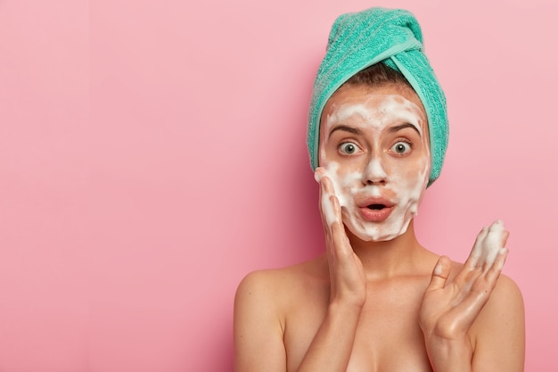 Photo of surprised european woman washes face with foam gel, wants to have refreshed well cared skin, stands topless, wears wrapped towel on wet hair, poses against pink background, free space aside Free Photo