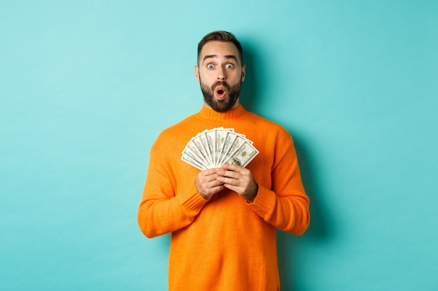 Photo of surprised guy holding money, looking amazed, standing with dollars against turquoise wall Free Photo