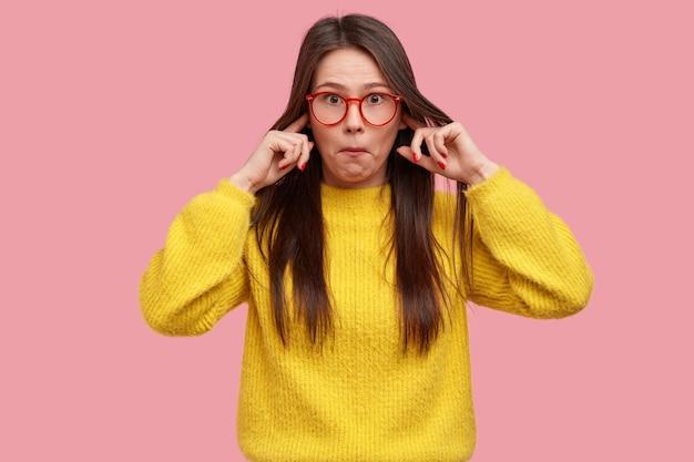 La foto di una signora sorpresa non sopporta un suono terribile, sorpresa dalle voci, tappi le orecchie, indossa abiti gialli Foto Gratuite