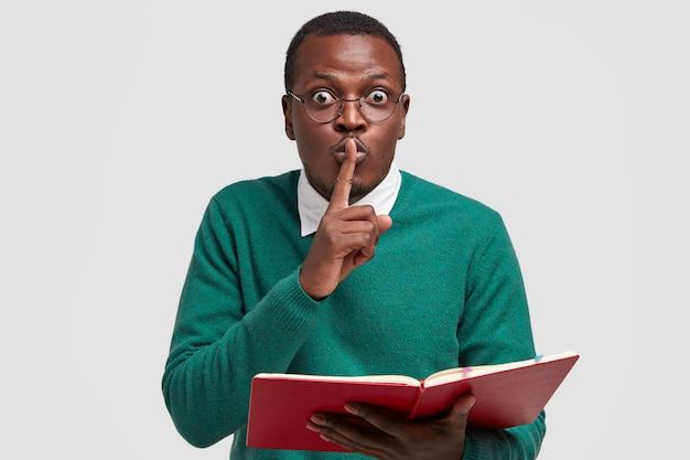 Photo of surprised male teacher holds fore finger over mouth, demonstrates shush gesture, reads textbook, asks to be quiet, wears glasses Free Photo