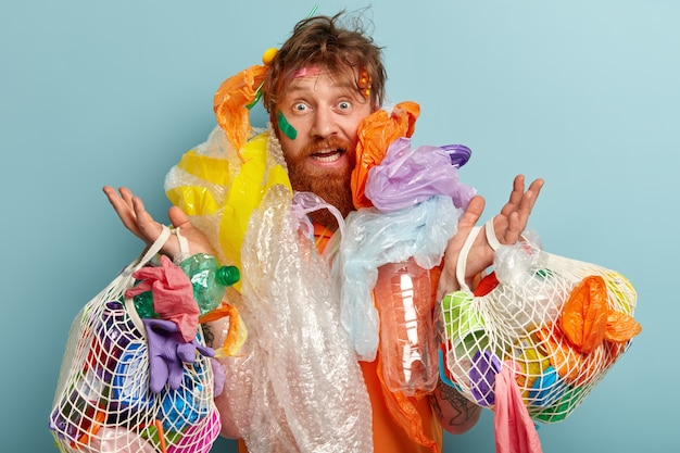Photo of surprised red haired man has thick beard, overloaded with much garbage, collects plastic Free Photo