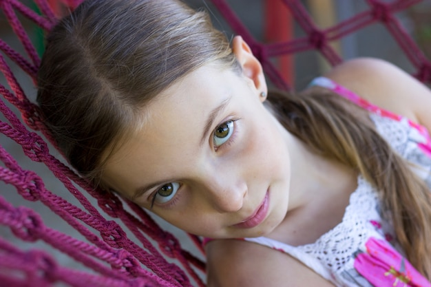 Photo of teen girl  lies on hammock during summer day and looking at camera Premium Photo