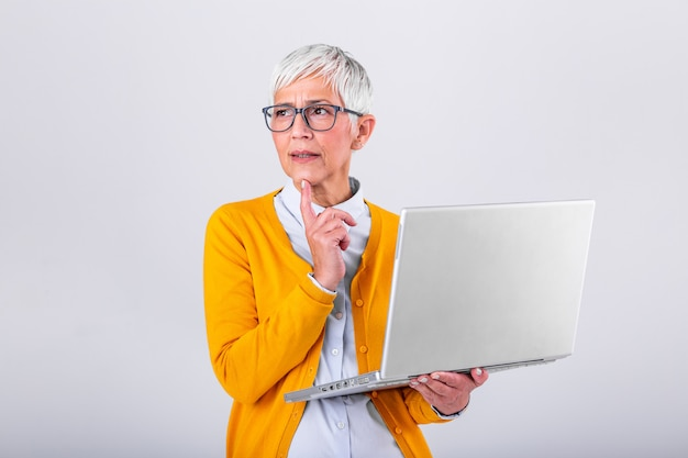 Photo of a thinking mature business woman isolated over grey background holding laptop computer. image of confused senior woman using laptop computer. looking at laptop while holding face with hands. Premium Photo
