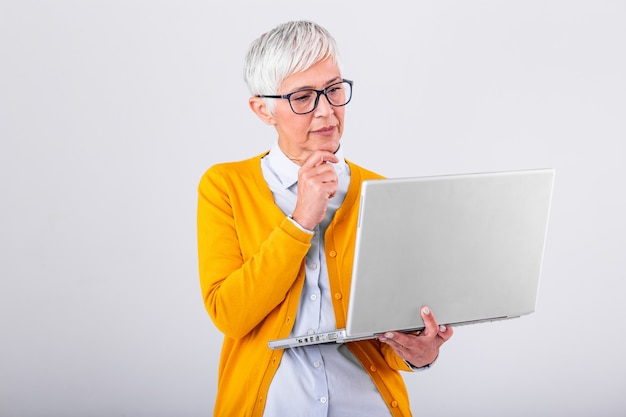 Photo of a thinking mature business woman isolated over grey background holding laptop computer. image of confused senior woman using laptop computer. Premium Photo