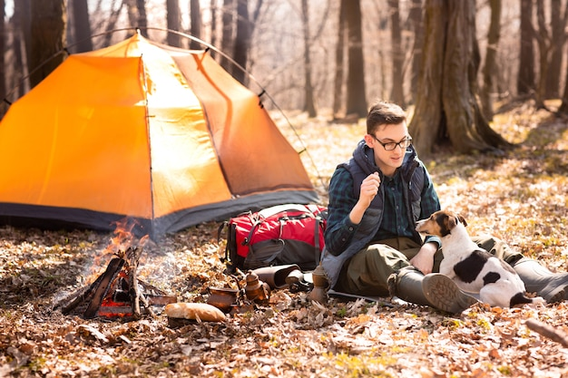 Photo of a tourist with a dog, resting in the forest near the fire and orange tent Premium Photo
