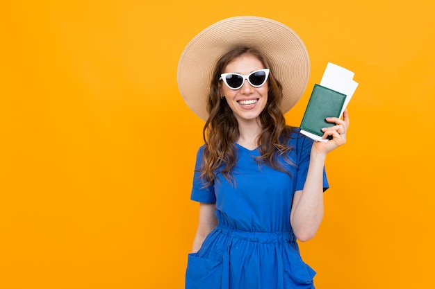Photo of a tourist with vacation tickets and passport on an orange background Premium Photo