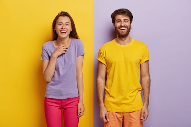 Photo of two delighted young woman and man stand together, express good emotions, smile happily Free Photo