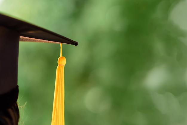 Behind photo of university graduate wears gown and black cap, yellow ribbon Premium Photo