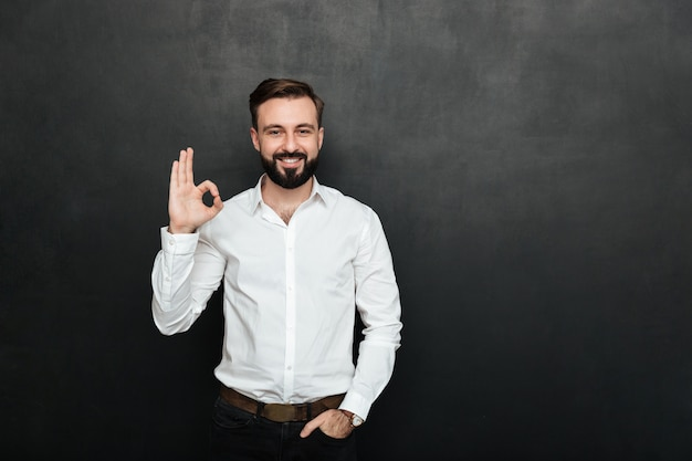 Photo of unshaved guy in office smiling and gesturing with ok sign expressing everything is alright, isolated over graphite Free Photo