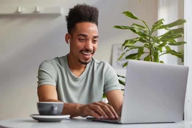 Foto di giovane ragazzo gioioso afroamericano attraente, lavora a un laptop si siede in un caffè, guarda il monitor e ampiamente sorridente, chiacchierando con la sua ragazza. Foto Gratuite