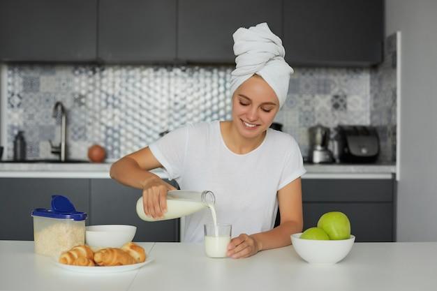 Foto di giovane donna bionda attraente si siede al tavolo la mattina, sorridente, guarda un bicchiere di latte Foto Gratuite
