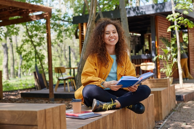 Photo of young attractive dark skinned curly student lady preparing for exam, siting on a cafe terrace, wearing in yellow coat, drink coffee, smiles broadly, enjoys studying. Free Photo