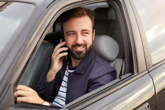 Foto di un giovane uomo barbuto attraente di successo in giacca blu e maglietta a righe, si siede al volante della macchina e aspetta una risposta al telefono. Foto Gratuite