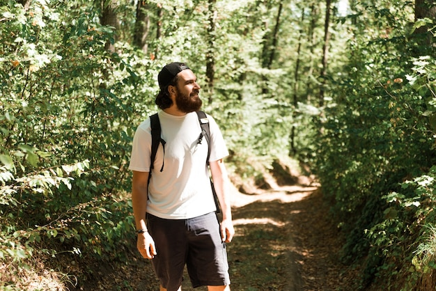 Photo of young bearded man hiking in forest during summer time, travel concept. Premium Photo