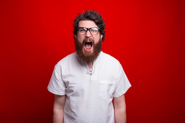 Photo of young bearded man screaming and looking at the camera Premium Photo