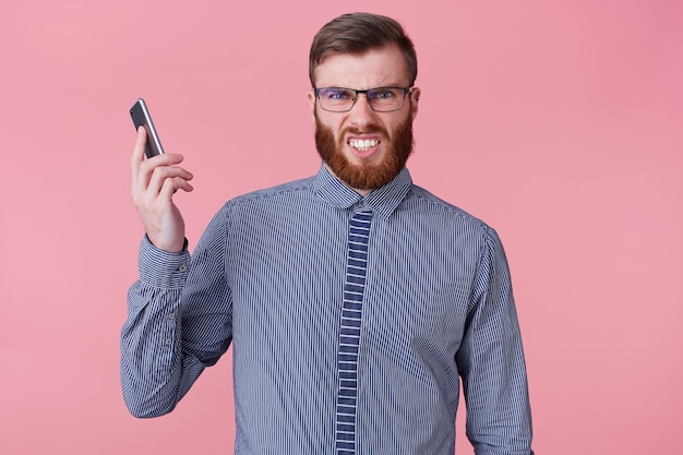 Foto di un giovane bell'uomo barbuto con gli occhiali e una camicia a righe, che tiene il telefono lontano dall'orecchio, perché chiamato da un capo furioso che prepara un telefono. isolato su sfondo rosa. Foto Gratuite