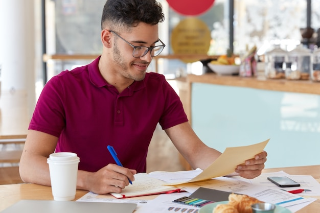 Photo of young inexperienced entrepreneur records information from business documents in notepad, studies graphics and charts, gets prepared for presenting information to investors, drinks coffee Free Photo