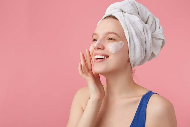 Photo of young nice joyful lady with natural beauty with a towel on her head after shower, stands and puts on face cream, looks away. Free Photo