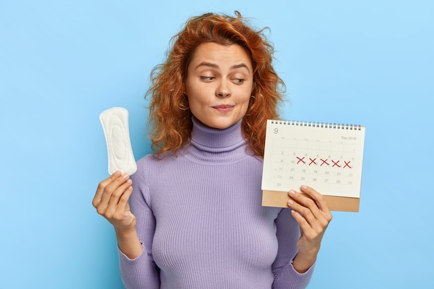 Photo of young woman looks at period calendar, checks menstruation days Free Photo