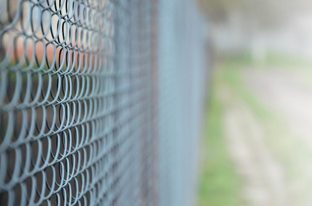 A photograph of a metal net used as a fence of private possessions. Premium Photo