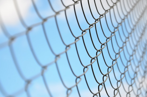 A photograph of a metal net used as a fence of private possessions Premium Photo