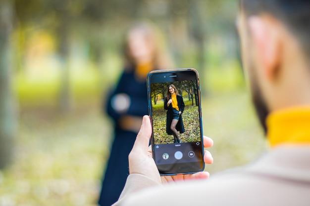 秋の公園で電話でガールフレンドの写真を撮る Premium写真