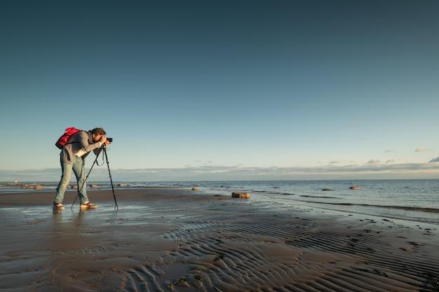 ビーチで三脚で立っている写真を作る写真家 Premium写真