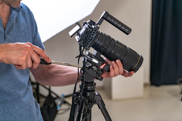 A photographer man tuns up a professional camera for work on the studio Premium Photo