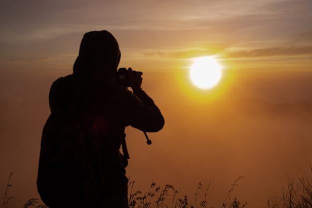 Un fotografo fotografa l'alba del sole sul vulcano batur. bali indonesia Foto Gratuite