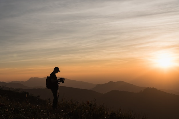 Photographer silhouettes on cliff against colorful twilight sky Premium Photo