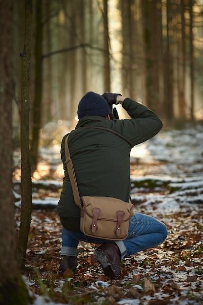 Fotografo che scatta foto in una foresta immersa nel verde ricoperta di neve e foglie Foto Gratuite