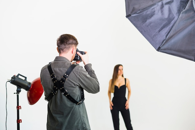 Photographer taking pictures of model in studio Free Photo