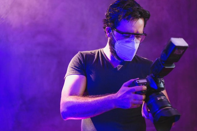 プロのカメラでkn95マスクを身に着けている写真家ビデオ制作の舞台裏、コロナウイルス保護のコンセプト Premium写真