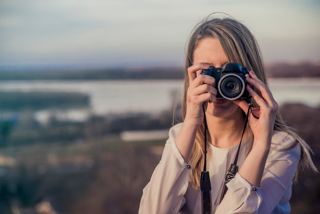 Photographer woman girl is holding dslr camera taking photographs. smiling young woman using a camera to take photo outdoors Free Photo